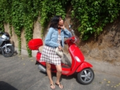Hispanic girl next to a Vespa