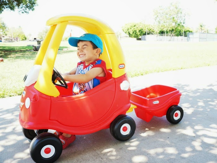 Boy riding the Cozy Coupe 30th Anniversary Edition with trailer // livingmividaloca.com