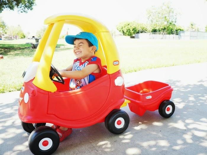 Boy riding the Cozy Coupe 30th Anniversary Edition with trailer // livingmividaloca.com