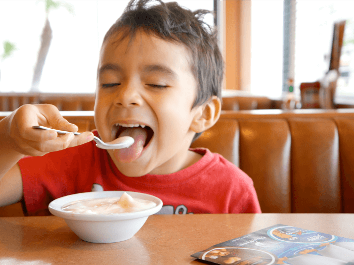 Boy eating yogurt at Denny's Diner
