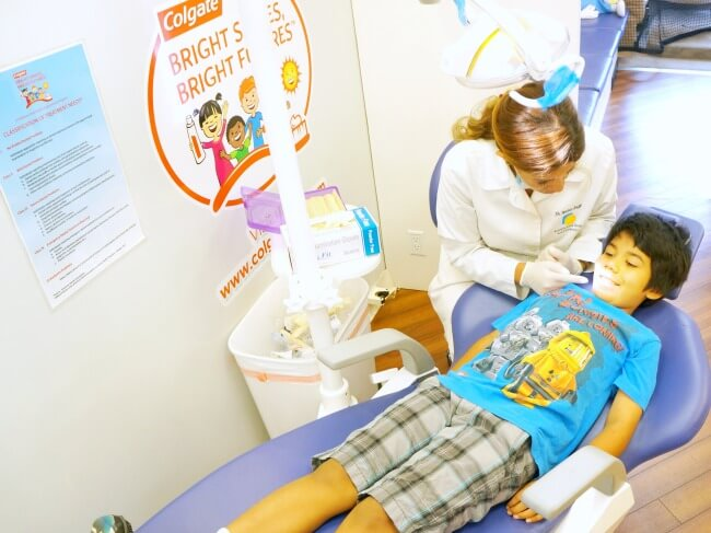 Boy getting teeth checked by dentist inside Colgate mobile dental unit