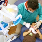Colgate dentist checking child's teeth