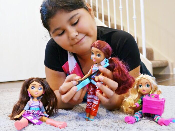 Hispanic girl playing with Vi and Va dolls