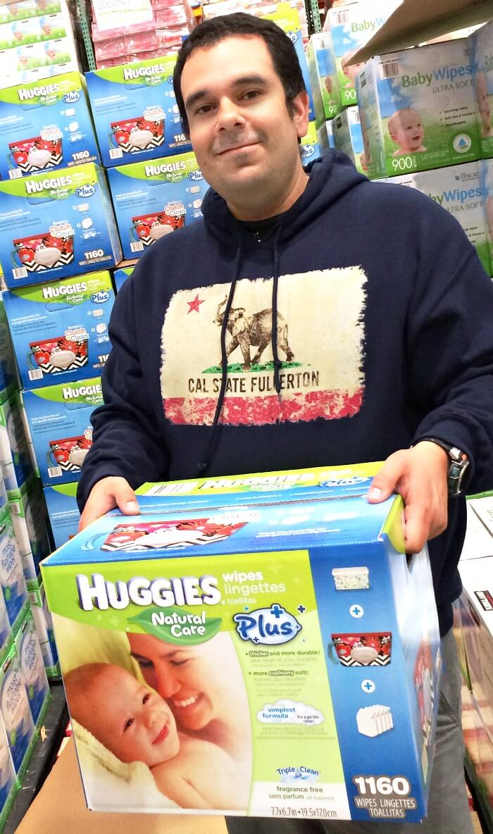 Latino dad buying Huggies Natural Care Plus Wipes, exclusively at Costco