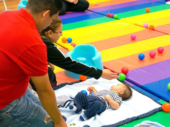 Latino parents playing with baby