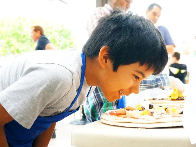 Boy smelling pizza // Pizza Party at Downtown Disney // LivingMiVidaLoca.com