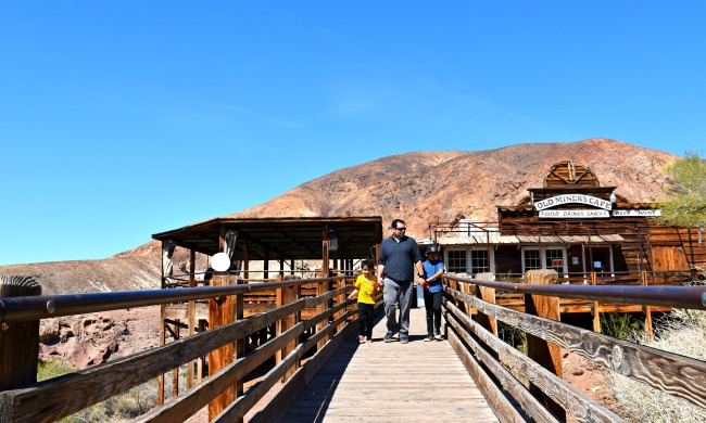 Dad and young boys walking down the bridge near the restaurant - Calico Ghost Town - Living Mi Vida Loca