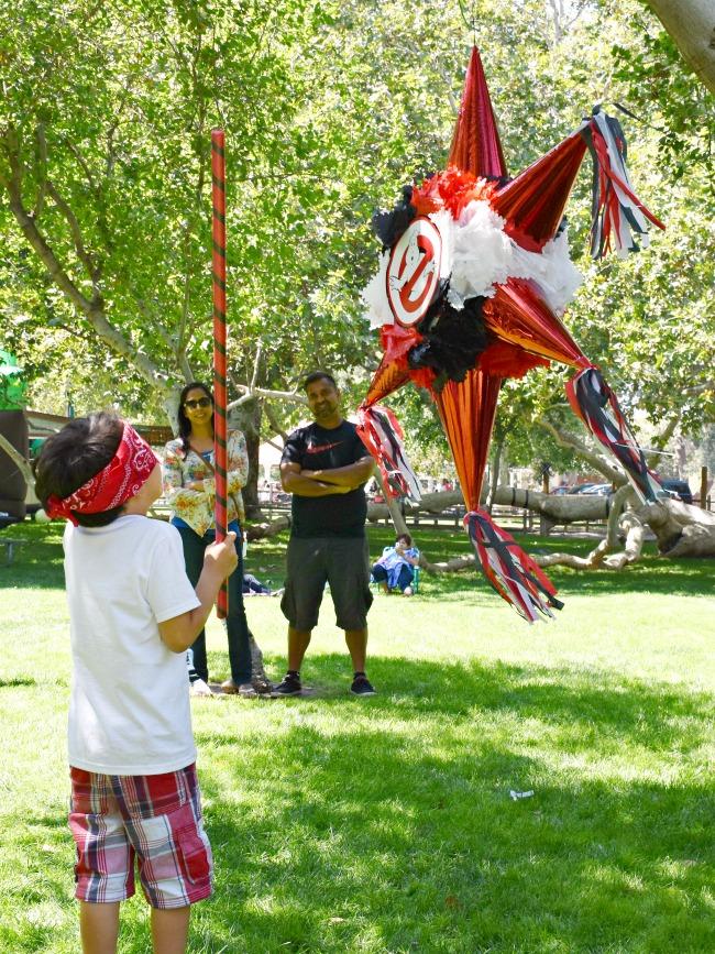 Boy hitting Ghostbusters piñata - Ghostbuster birthday party - LivingMiVidaLoca.com - #LivingMiVidaLoca #birthdaypartyideas #Ghostbusters