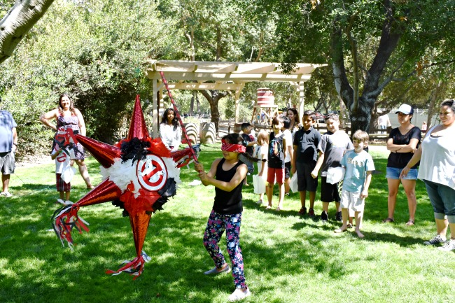 Girl hitting Ghostbusters piñata : Ghostbuster Party : LivingMiVidaLoca.com (photo credit: Pattie Cordova)