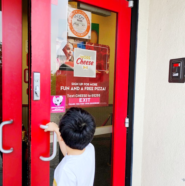 Kid opening up door at Chuck E Cheese - livingmividaloca.com