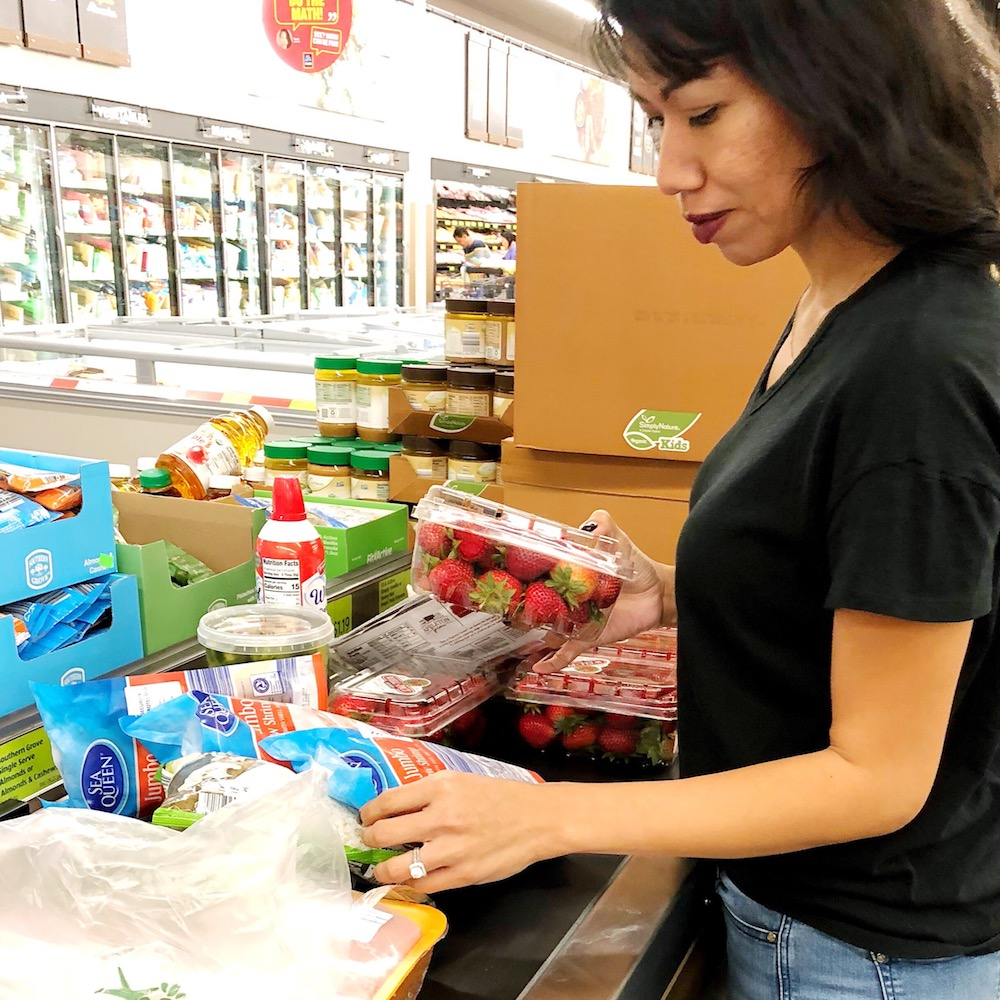 Latina woman checking out at grocery store with keto foods - livingmividaloca.com