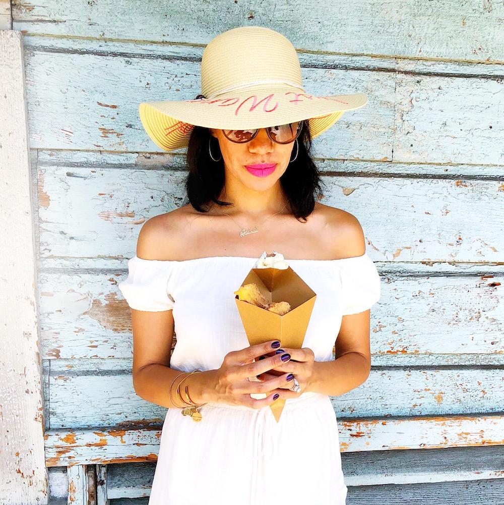 Girl holding churro bites wearing a white sunhat - livingmividaloca.com