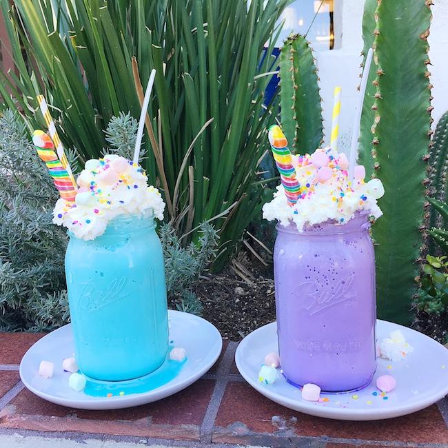 Unicorn milkshake in purple mason jar topped with whipped cream, sprinkles, lollipop and marshmallows. #unicornfoods #unicornmilkshake #unicorns #partyfood #unicornparty #unicorntreats #unicornpartytreats  livingmividaloca.com