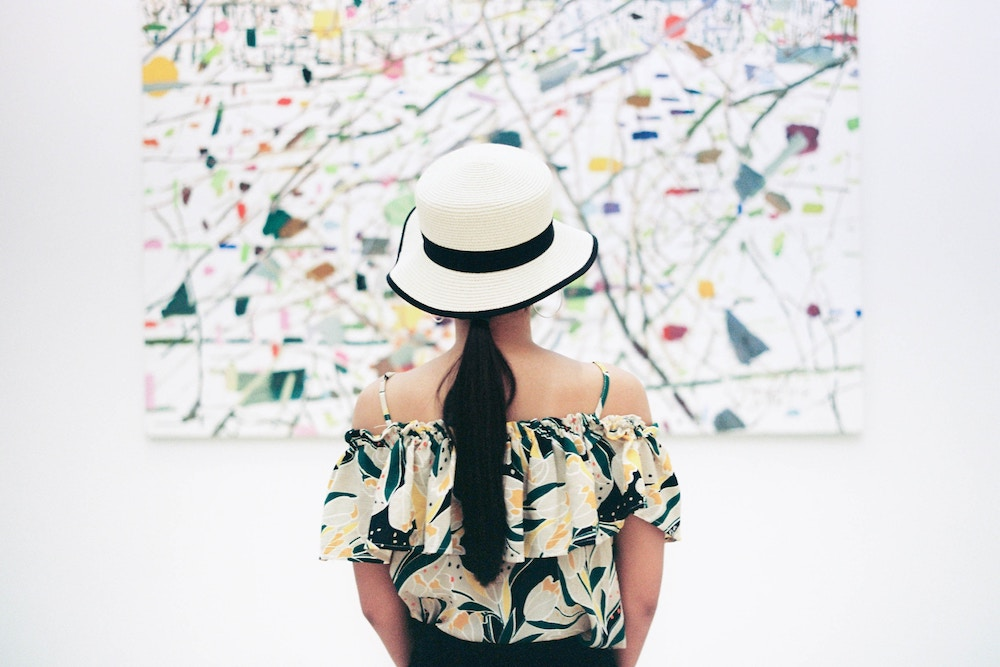 young woman wearing white hat standing looking at artwork