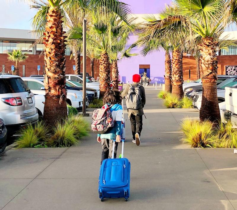 Boys carrying luggage traveling to Mexico via CBX - livingmividaloca.com - #LivingMiVidaLoca #LMVLSoCal #CBX #FamilyTravel